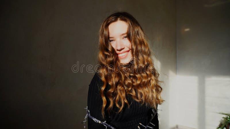 Het jonge Vrouwelijke Glimlachen, die Camera met krullend haar bekijken royalty-vrije stock afbeeldingen