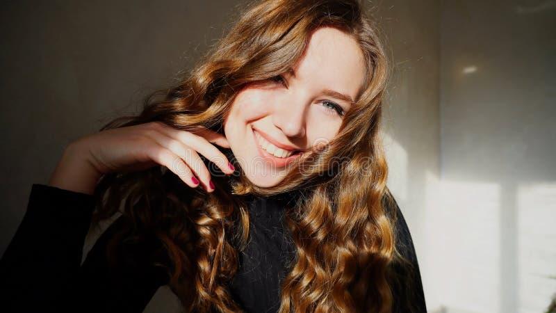 Het jonge Vrouwelijke Glimlachen, die Camera met krullend haar bekijken royalty-vrije stock foto's