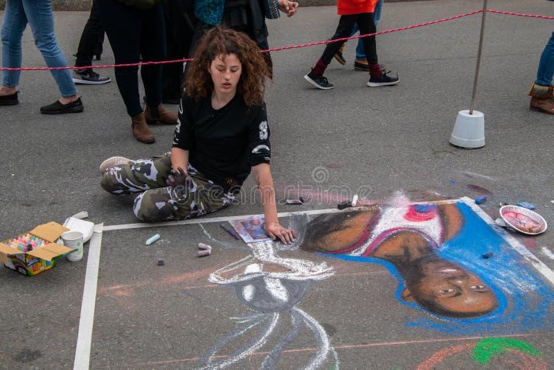 Het jonge vrouwelijke Kaukasische student situeren op de straat en trekt een muurschildering met krijt zoals die op deze datum wo stock foto