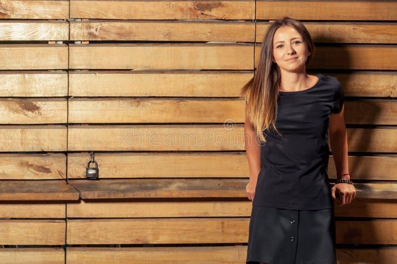 Het jonge vrouwelijke model stellen op houten poortachtergrond royalty-vrije stock fotografie