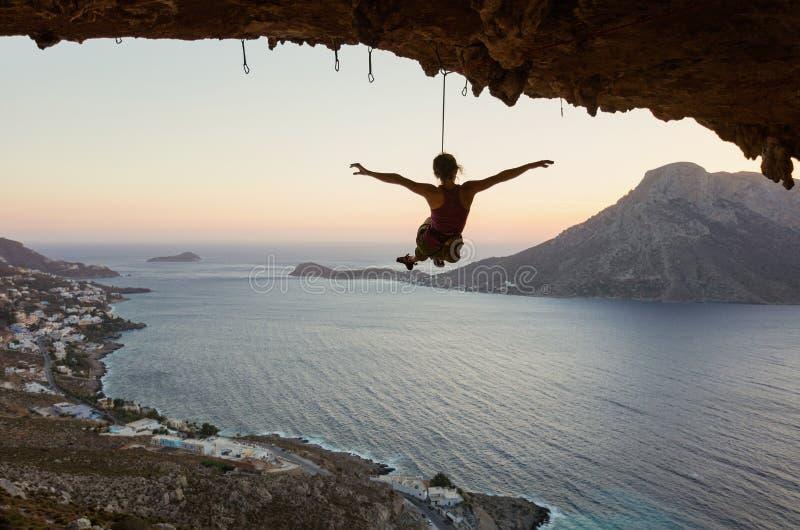 Het jonge vrouwelijke rotsklimmer hangen op kabel en uit het uitrekken van wapens royalty-vrije stock foto