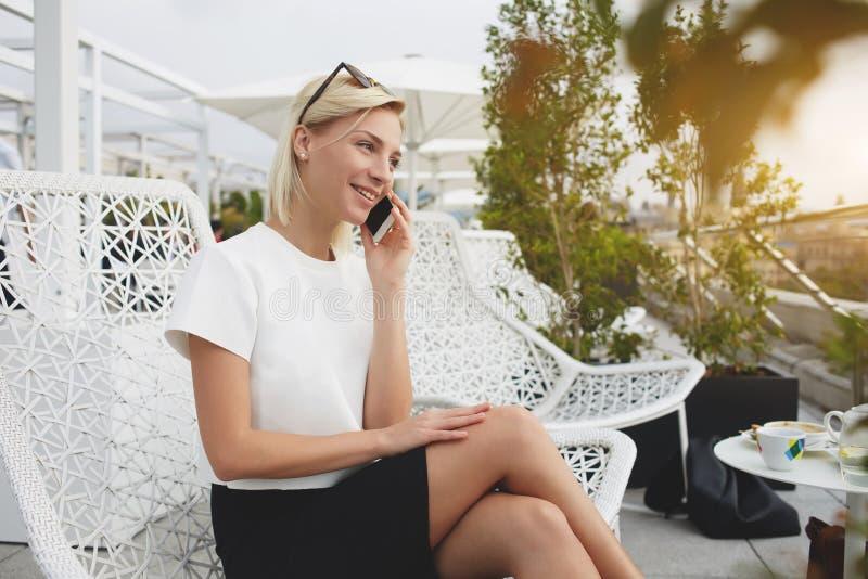 Het jonge vrouwelijke spreken op mobiele telefoon terwijl in openlucht het zitten stock foto's