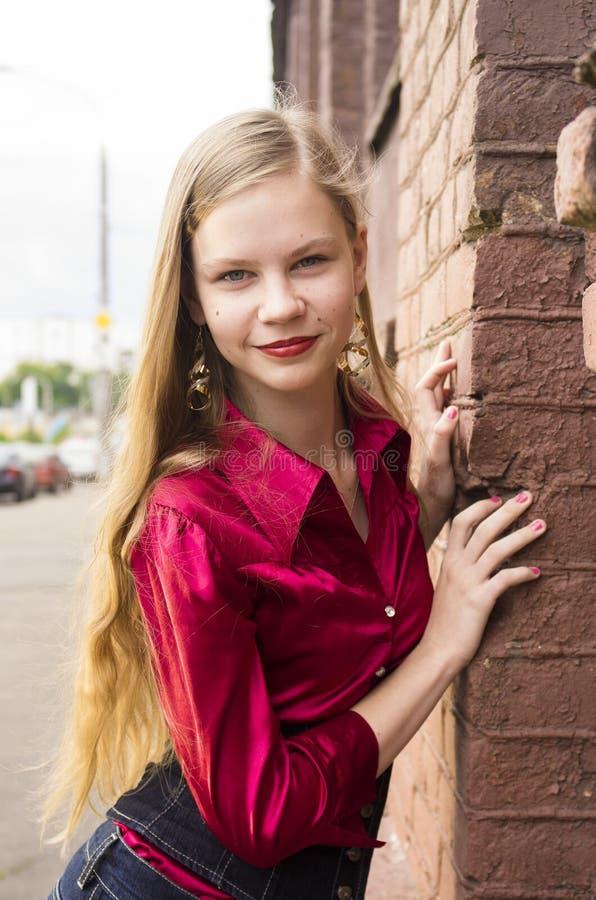 Het jonge vrouwelijke tienermeisje stelt tegen een bakstenen muur royalty-vrije stock afbeeldingen