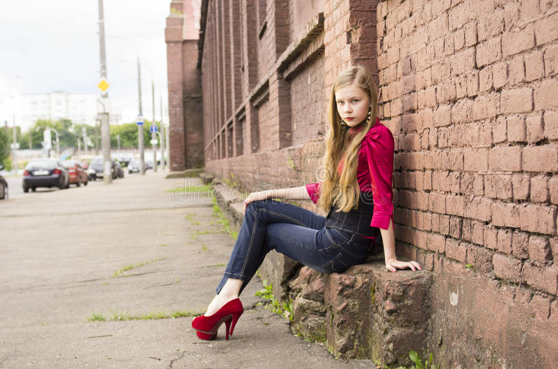 Het jonge vrouwelijke tienermeisje stelt tegen een bakstenen muur royalty-vrije stock fotografie