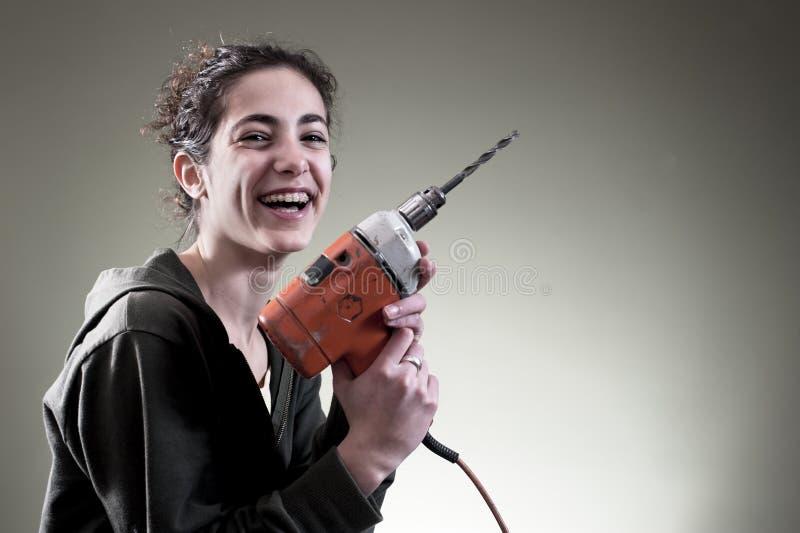 Het jonge vrouwelijke werken met boor stock foto