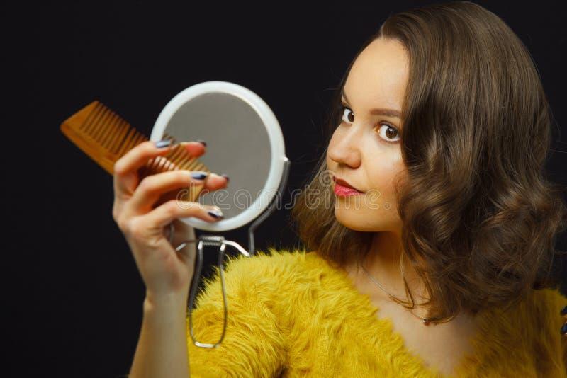 Het jonge vrouwen correctslight bruine haar en houdt spiegel, kam in haar handen op geïsoleerde zwarte stock foto