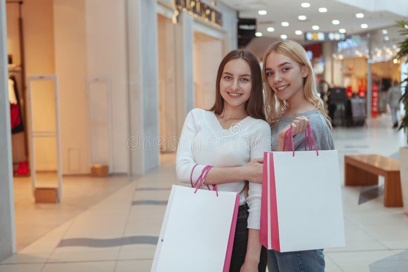 Het jonge vrouwen genieten die samen bij de wandelgalerij winkelen royalty-vrije stock afbeeldingen