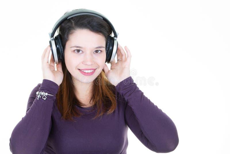 Het jonge vrouwenbrunette met hoofdtelefoons kijkt in camera kopieert opzij ruimte stock afbeelding