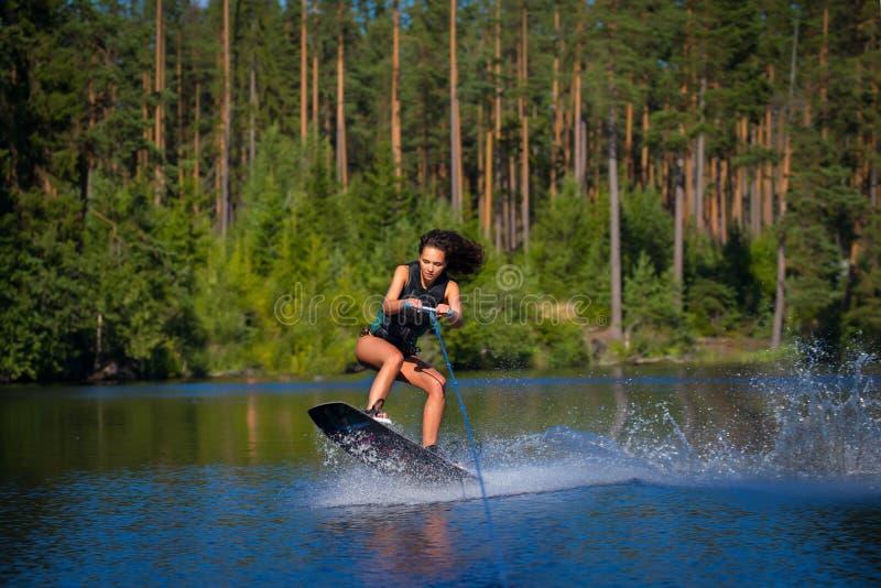 Het jonge vrouwenstudie het berijden wakeboarding op een meer stock afbeelding