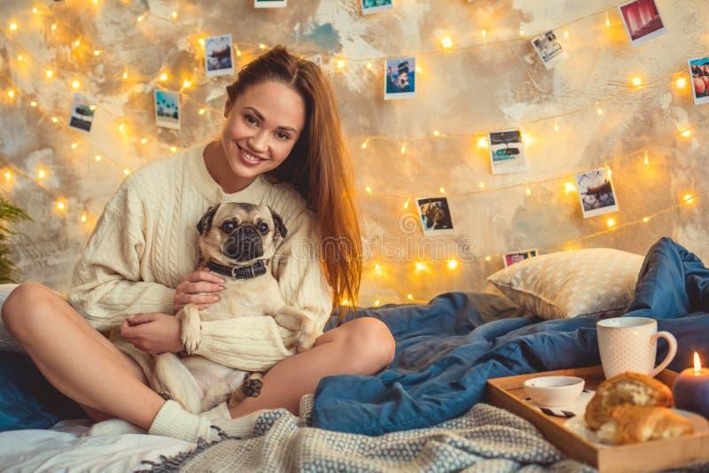 Het jonge vrouwenweekend verfraaide thuis slaapkamer koesterend een hond stock fotografie
