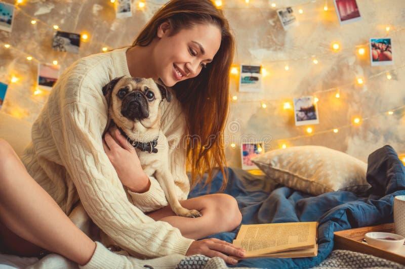 Het jonge vrouwenweekend verfraaide thuis slaapkamer met het boek van de hondlezing stock afbeelding