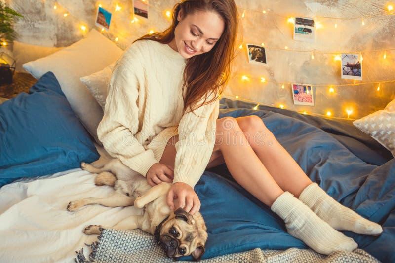 Het jonge vrouwenweekend verfraaide thuis slaapkamer het spelen met hond stock foto