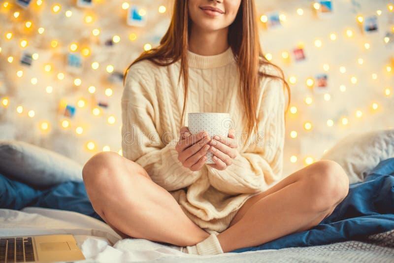 Het jonge vrouwenweekend verfraaide thuis slaapkamerzitting die hete thee houden royalty-vrije stock foto's