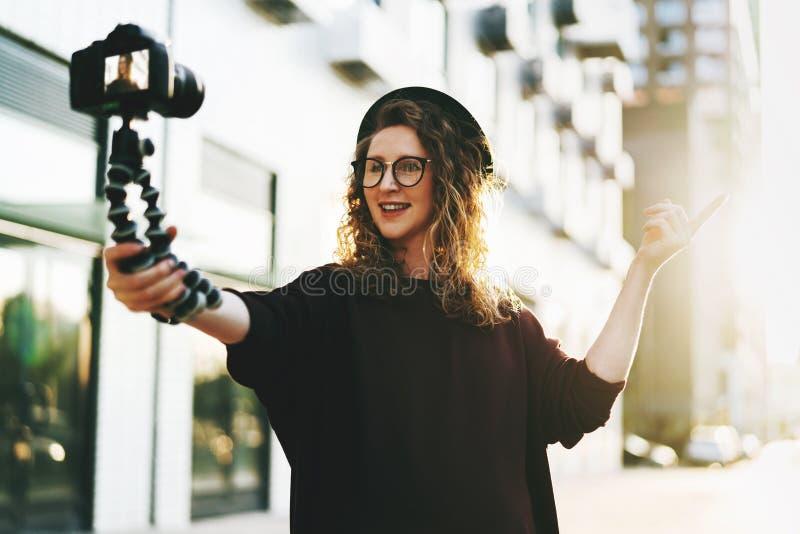 Het jonge wijfje blogger in in glazen en hoedengangen op stadsstraat, registreert zich op videoholdingscamera voor driepoot royalty-vrije stock foto