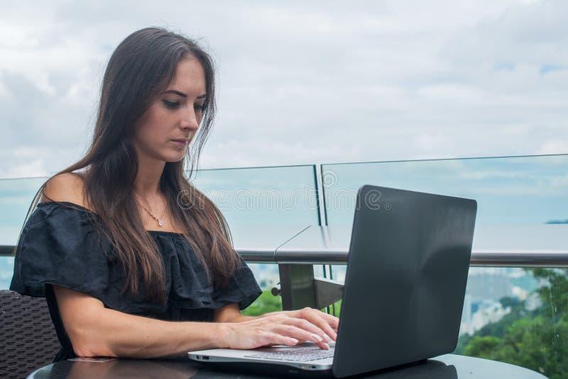 Het jonge wijfje freelancer kleedde zich in het zwarte werken aan een projectlaptop computer terwijl het zitten bij het terras va stock foto's
