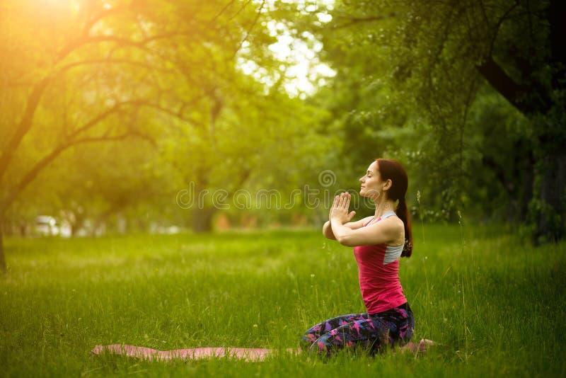 Het jonge wijfje in ochtendtuin het praktizeren yoga in diamant stelt royalty-vrije stock foto's