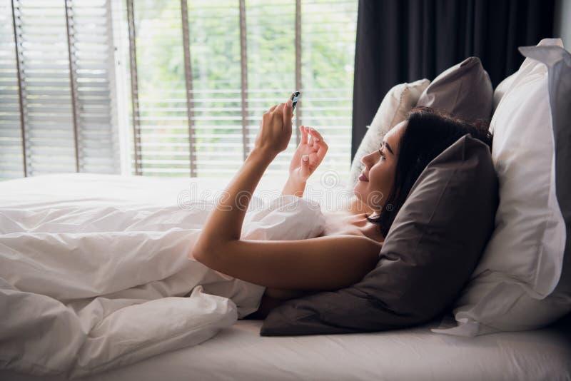 Het jonge wijfje verbindt sociaal netwerk aan smartphone in de ochtend, ontspant zij op wit bed royalty-vrije stock afbeelding