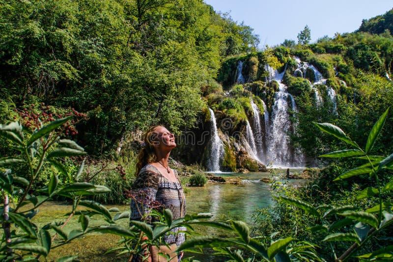 Het jonge witte vrouwelijke toerist glimlachen die de zon op de achtergrond van de mooie complexe waterval van Plitvice bekijken stock foto's