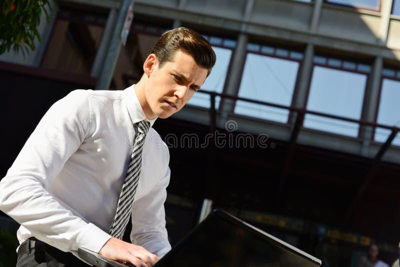 Het jonge zakenman typen in een laptop computer in stedelijke backgroun royalty-vrije stock afbeeldingen