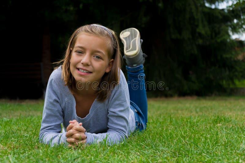 Het jonge zigeunermeisje legt in gras het glimlachen stock afbeelding