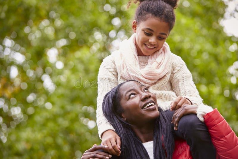 Het jonge zwarte die haar pre-tienerdochter op haar schouders in het park vervoeren, allebei die bij elkaar glimlachen, sluit omh royalty-vrije stock foto's