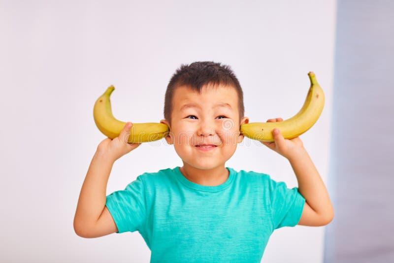 Het jongenskind behandelde zijn oren met bananen royalty-vrije stock afbeelding