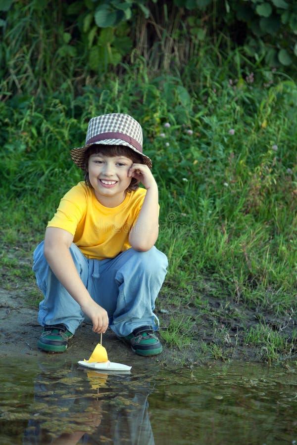 Het jongensspel met het schip van het de herfstblad in water, kinderen in park speelt wi stock fotografie