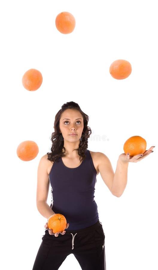 Het jongleren met van de vrouw sinaasappelen stock afbeeldingen
