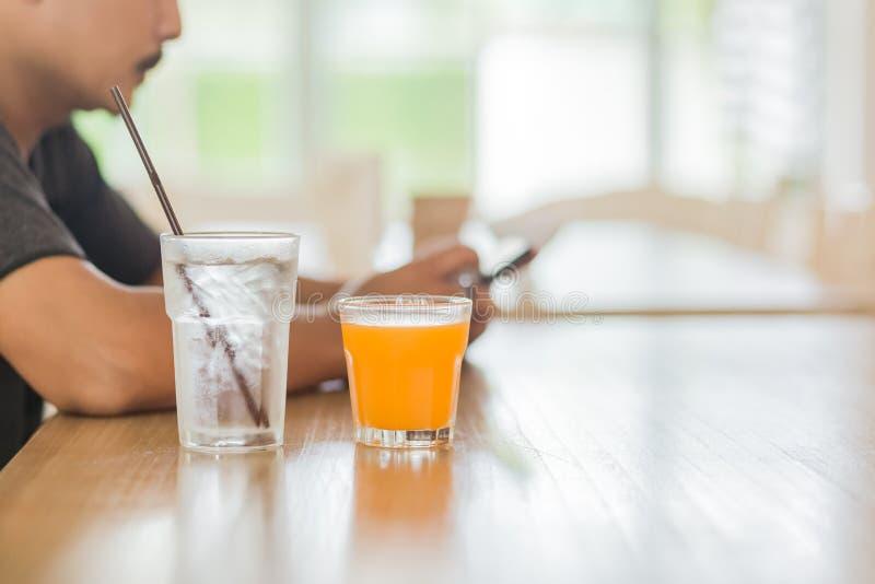 Het jus d'orange in glas op de lijst dichtbij waterijs stock afbeeldingen