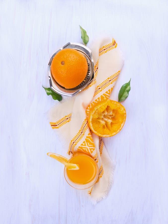 Het jus d'orange, het Gedrukte fruit en de roestvrij staalcitrusvrucht juicer op blauw woden stock afbeelding