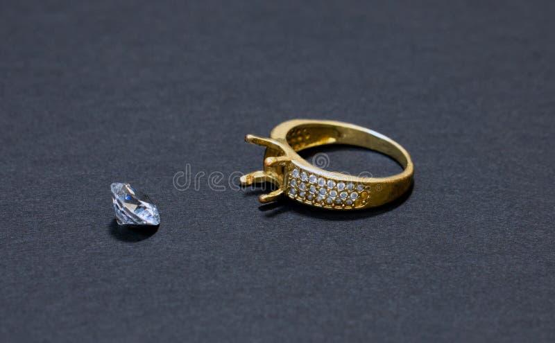 Het juwelenwerk, gouden ring met een diamant, voorbereiding voor het installeren van een steen op een ring, donkere achtergrond stock afbeelding