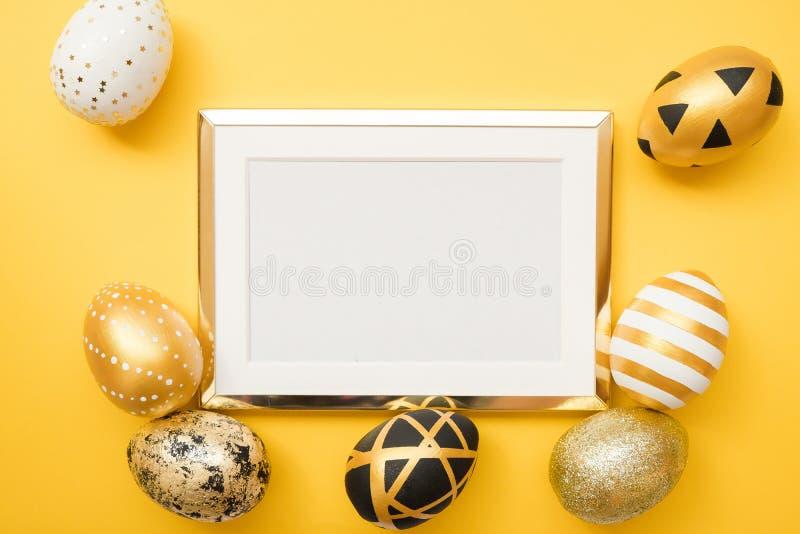 Het kader met goud verfraaide paaseieren met exemplaarruimte voor tekst op gele achtergrond Minimaal Gelukkig Pasen-concept Hoogs stock afbeeldingen