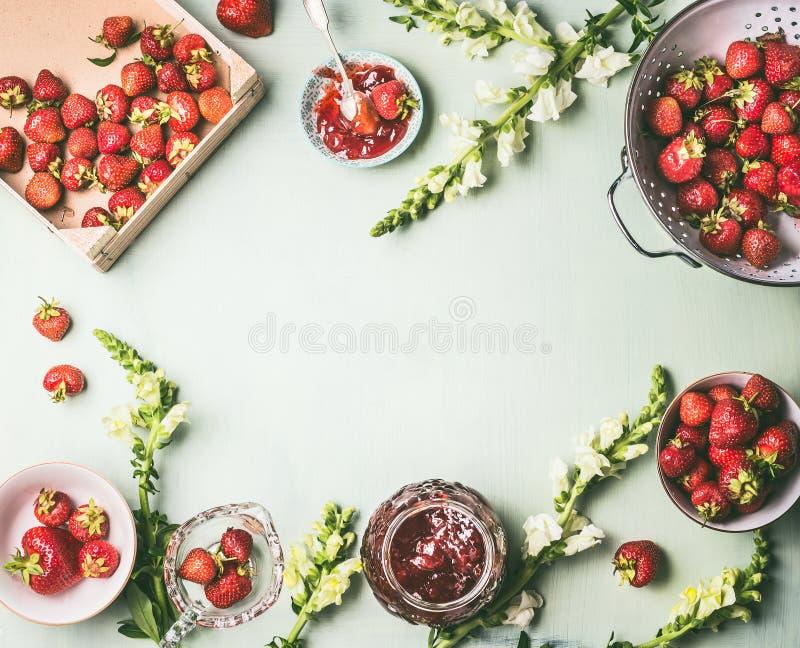 Het kader met verse aardbeien in vergiet en kommen met jampot wordt gemaakt en de lepel op keuken dienen achtergrond met tuinbloe stock afbeeldingen