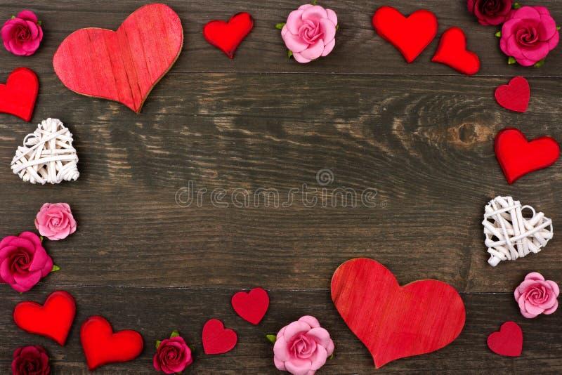Het kader van de valentijnskaartendag van houten harten en document bloemen tegen donker hout stock fotografie