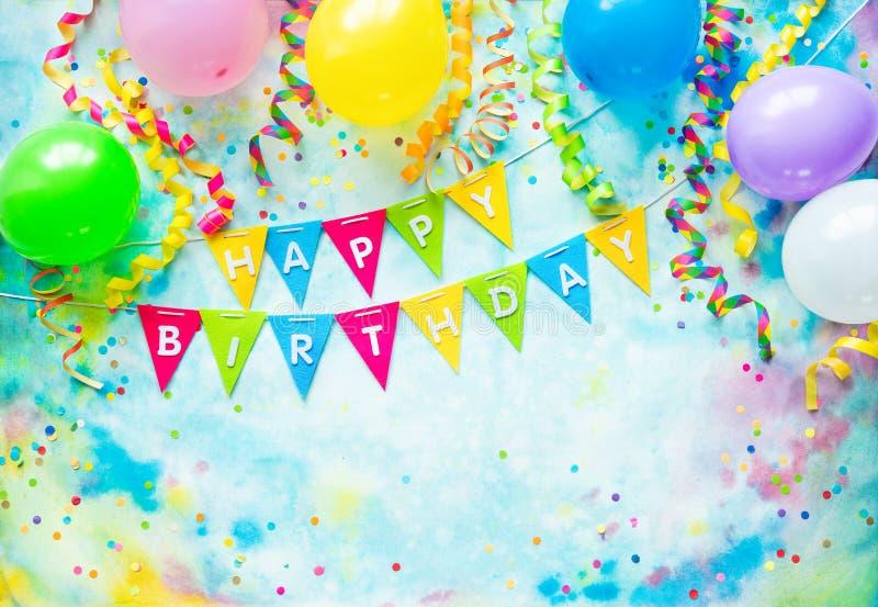 Het kader van de verjaardagspartij met ballons, wimpels en confettien op kleurrijke achtergrond met exemplaarruimte royalty-vrije stock foto's