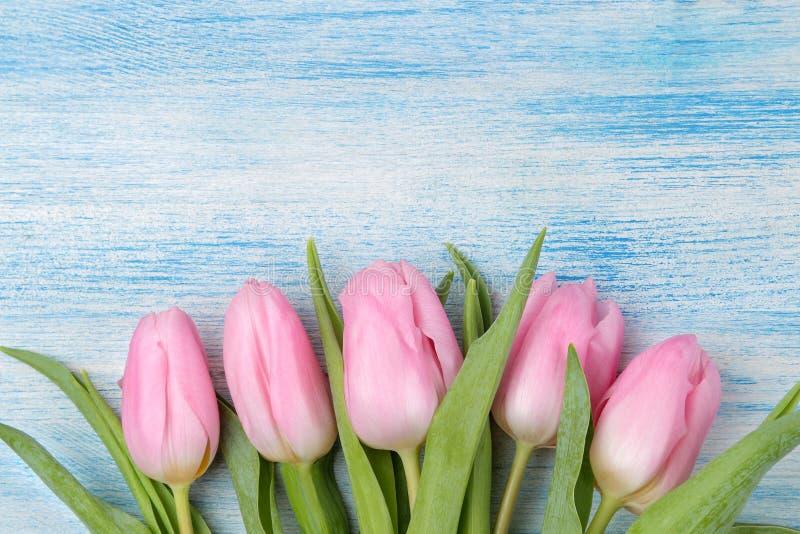 Het kader van een mooi boeket van roze tulpen bloeit op een blauwe houten achtergrond Hoogste mening ruimte voor de tekstlente va royalty-vrije stock fotografie
