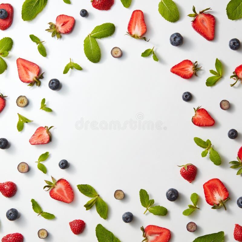 Het kader van fruitpatroon met aardbeien, bosbessen en muntbladeren op een witte vlakke achtergrond, legt royalty-vrije stock afbeelding