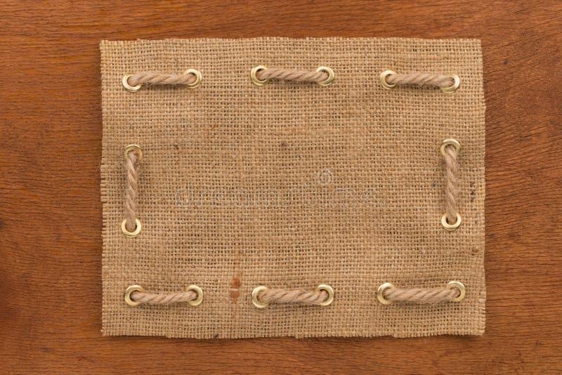 Het kader van jute met een kabel wordt gemaakt door in gouden ringen wordt ingepast, ligt op een houten oppervlakte die stock foto