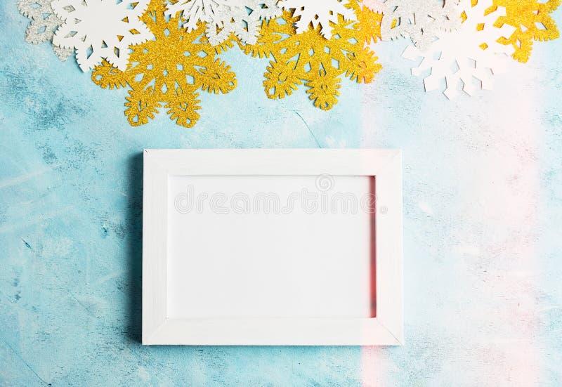 Het kadermodel van de Kerstmisfoto: witte, gouden en zilveren document sneeuwvlokken op blauwe achtergrond lettering royalty-vrije stock afbeelding