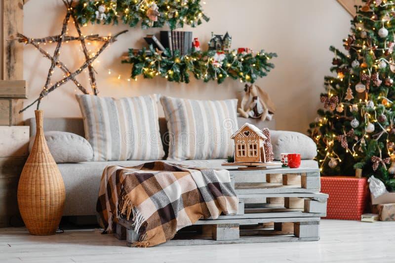 Het kalme beeld van binnenlandse moderne die huiswoonkamer verfraaide Kerstmisboom en giften, bank, lijst met deken wordt behande stock foto's