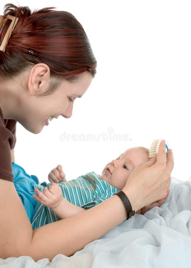 Het kammen van baby`s haar stock foto's