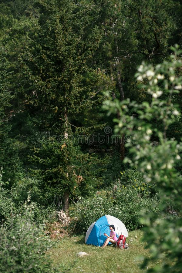 Het kamperen in de bergen Een vrouw zit dichtbij tent tegen de achtergrond van groene bomen en bergen stock afbeelding