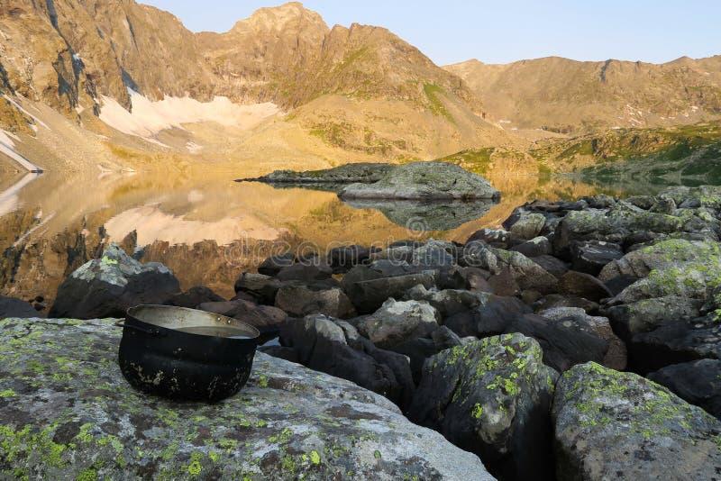 Het kamperen de pot met water op de achtergrond van bergen weerspiegelt bezinning in het meer Wandelings motievenbeeld stock afbeeldingen