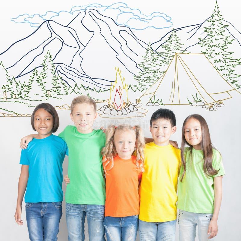 Het kamperen en de vakantie van de kampvuurzomer, groep kinderen bij bergkamp stock foto's