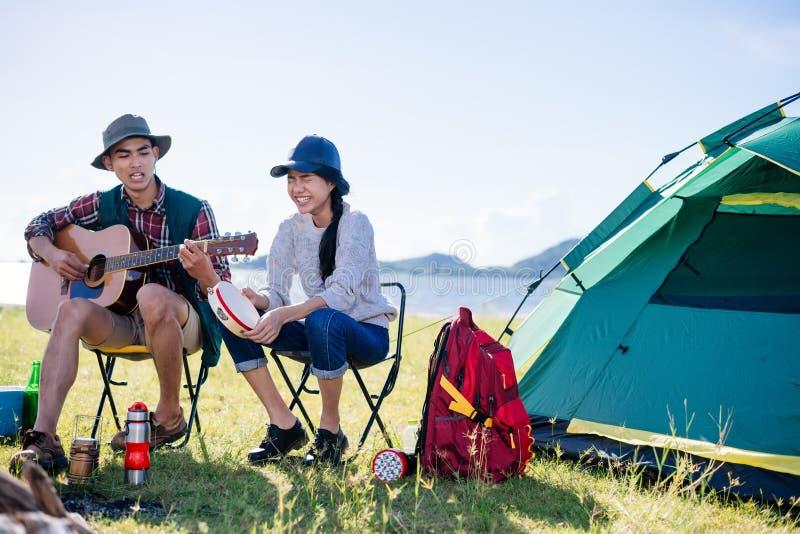 Het kamperen kamp in partij van aard de gelukkige vrienden en het spelen gitaar aan royalty-vrije stock afbeeldingen