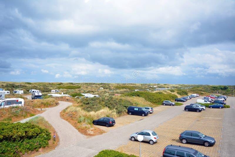Het kamperen plaats met grote die autoparkeerplaats 'Kogerstrand 'in de duinen dichtbij strand wordt genoemd stock afbeeldingen