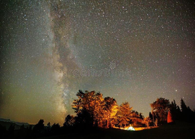 Het kamperen tent onder sterren bij nacht stock afbeelding