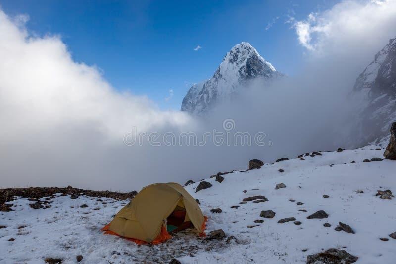 Het kamperen tent in sneeuwbergen royalty-vrije stock afbeeldingen