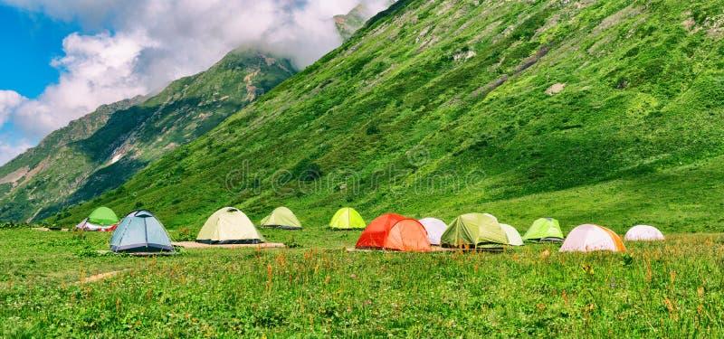 Het kamperen tenten in kampeerterrein bij bergenachtergrond royalty-vrije stock foto's