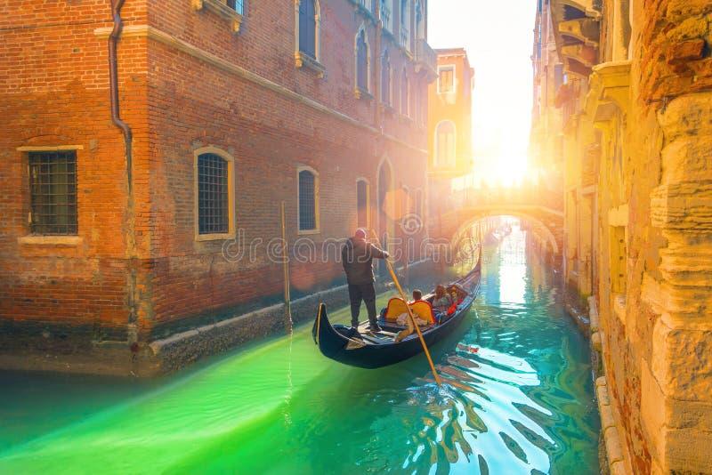 Het kanaal, de gondel en de gondelier van Venetië met toeristen die door water in de stad reizen royalty-vrije stock foto's